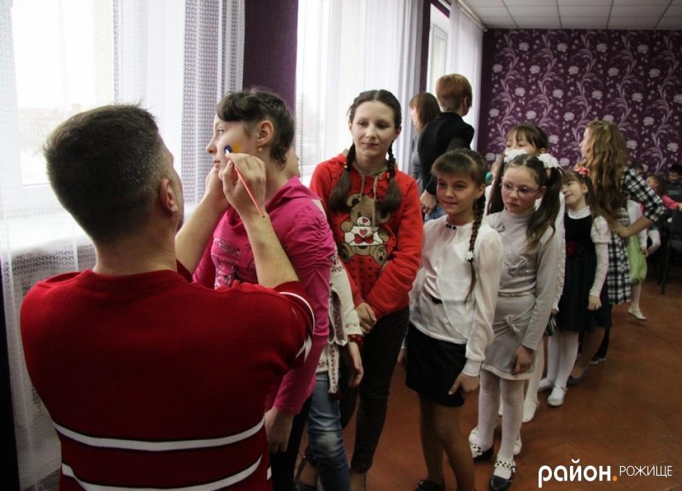 Художник Віталій Шевченко малює на щічках учасників свята патріотичні серця
