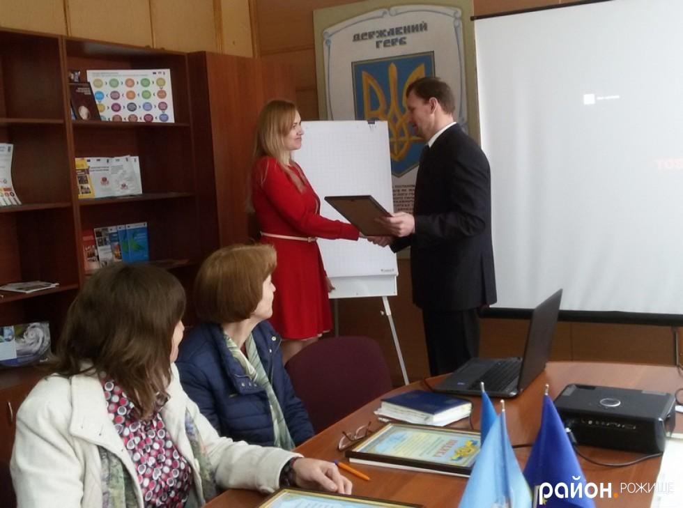 Голова райради Андрій Музика вручає подяку координатору обласного ресурсного центру громад Ірині Бойко